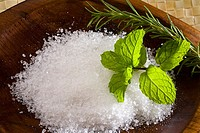 Spa elements, koa bowl filled with raw salt, garnished with a sprig of mint and rosemary