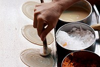 Thailand, Bangkok, Close-up of hands spooning batter onto a hot skillet to make Thai style pancakes