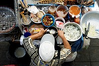 Thailand, Bangkok, View from above of a street food stall with vendor prepping food