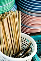 Thailand, Bangkok, Chopsticks, silverware and stacks of dishes at a street food stall