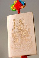 Close-up of a hanging Chinese decoration depicting Buddha on a wooden tablet