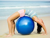 Woman bending over exercise ball