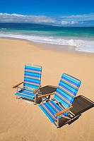 Brightly colored beach chairs on the sand near the ocean