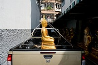Thailand, Bangkok, Buddha tied down by it's crown in the bed of a truck