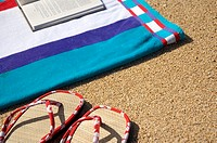 Red edged slippers and corner of beach towel with book on sand (thumbnail)