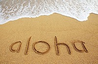 Aloha written in sand with wave wash