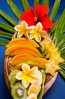 Studio shot pf a variety of tropical fruit sliced on a platter, with flowers (thumbnail)