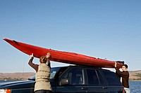 Couple Taking Kayak from Car Roof