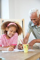 Girl and grandfather coloring in notebook