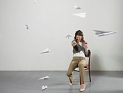 Businesswoman throwing paper airplanes (thumbnail)