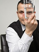 Businessman looking through drinking glass