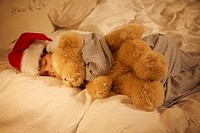 Child sleeping in a Santa hat