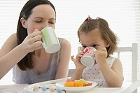 Mother and daughter drinking from cups