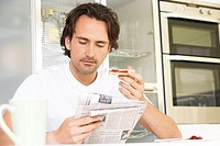 Man reading newspaper and eating toast