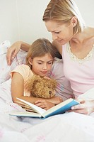 Mother reading book in bed