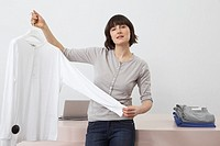 Salesgirl showing white shirt on hanger