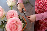 Florist cutting rafia on flower arrangement