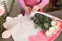 Florist wrapping bouquet of pink roses