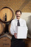 Winemaker carrying box in wine cellar