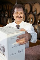 Winemaker holding box in wine cellar