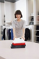 Saleswoman placing stack of folded pants on counter