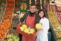Couple holding crate of melons