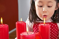 Young girl blowing out Christmas candles