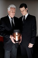 Men Looking at Funeral Urn