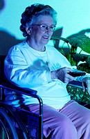 A senior woman holding a remote control, watching TV