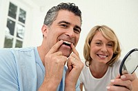 Mature man applying a teeth whitening strip to his teeth with a mid adult woman holding a mirror