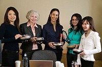 Five businesswomen standing and holding packaged meals