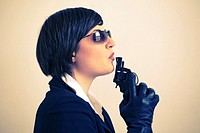 Woman with sunglasses blowing pistol (thumbnail)