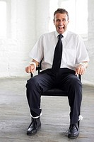 Tied up businessman screaming for help