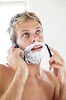 Bare chested man shaving while talking on the mobile phone