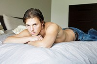 Man lying forward on the bed staring at the camera