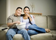Asian couple sitting on sofa with popcorn
