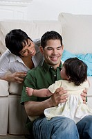 Hispanic parents smiling at baby