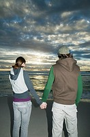 Young couple holding hands on beach, rear view, dusk