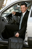 Hispanic businessman getting out of car