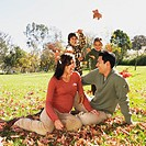 Hispanic family playing in autumn leaves