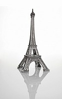 Silver Eiffel Tower model, against white background, close-up