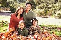 Hispanic family sitting in autumn leaves