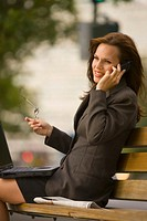 Businesswoman sitting on bench with laptop, using mobile phone, smiling