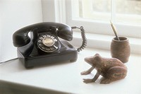 ´Old fashioned telephone on window sill, model frog and pen holder beside, close-up´