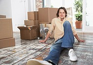 Man sitting on hardwood floor with cardboard boxes and potted plants smiling