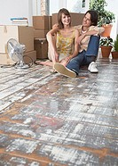 Man and woman sitting on hardwood floor with cardboard boxes and fan