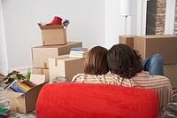 Rear view of couple on red chair in house with cardboard boxes (thumbnail)