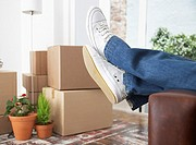 Man lying down on sofa in home with cardboard boxes