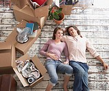 Man and woman laying down on hardwood floor with cardboard boxes