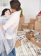 Man and woman embracing with bubble wrap in home with cardboard boxes